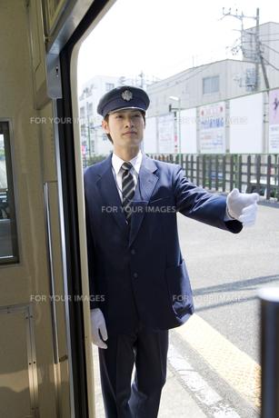 電車の出発アナウンスをする駅員の写真素材 [FYI00479883]