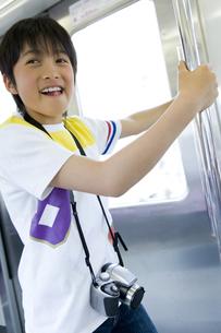 電車内の手すりにつかまる男の子の写真素材 [FYI00479898]