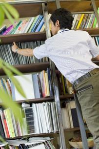 本棚から本をとる男性の写真素材 [FYI00479927]