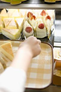 ショウケースからケーキを取り出す女性スタッフの写真素材 [FYI00480034]
