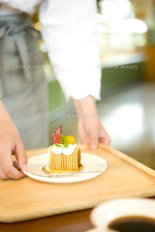 テーブルへケーキを運ぶ女性スタッフの写真素材 [FYI00480061]