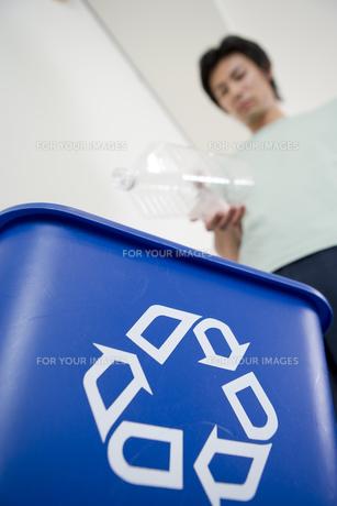 ペットボトルを回収箱に入れようとする男性の写真素材 [FYI00480140]