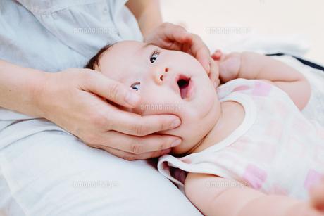 お母さんにほっぺを挟まれる赤ちゃんの写真素材 [FYI00481488]