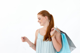Beautiful teenager withholding shopping bags and a credit cardの写真素材 [FYI00482067]
