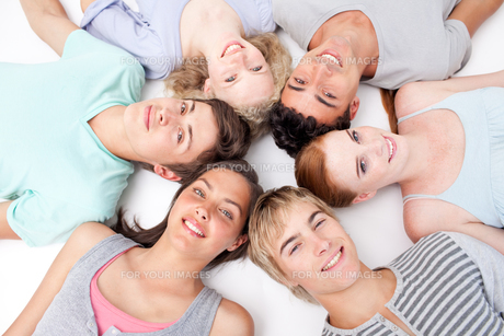 Friends lying on floor with heads togetherの写真素材 [FYI00482068]