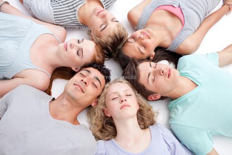 Teens sleeping on floor with heads togetherの素材 [FYI00482069]