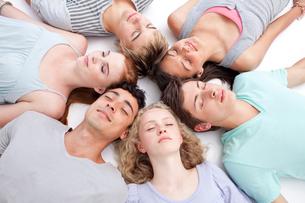 Teens sleeping on floor with heads togetherの写真素材 [FYI00482069]