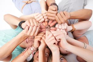 Teens lying on floor with thumbs upの素材 [FYI00482071]