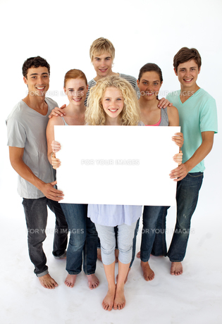 Group of teenagers holding a blank cardの写真素材 [FYI00482072]