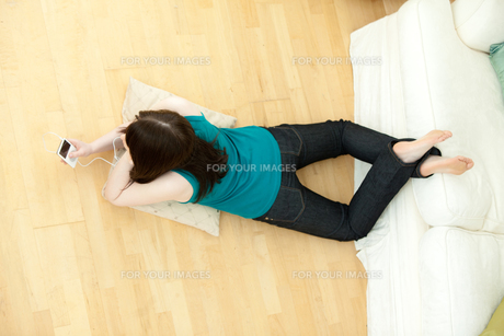 Young woman listening music lying down on the floorの写真素材 [FYI00482092]