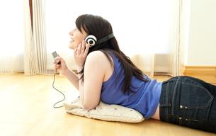 Happy woman listening music lying on the floorの素材 [FYI00482097]