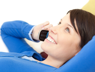 Attractive young woman talking on phone lying on a sofaの写真素材 [FYI00482098]