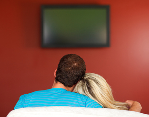 Couple sitting on couch watching a television at homeの写真素材 [FYI00482104]