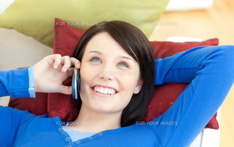 Beautiful teen girl talking on phone lying on a sofaの写真素材 [FYI00482105]