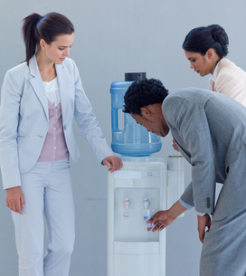 Business people drinking from a water coolerの写真素材 [FYI00482122]