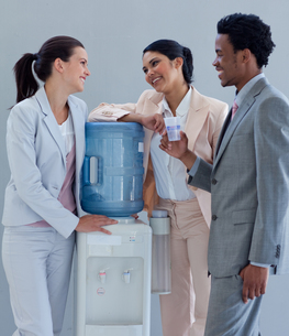 Business people speaking next to a water coolerの写真素材 [FYI00482123]
