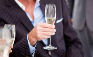 Close up of a senior businessman holding a glass of Champagneの写真素材 [FYI00482148]