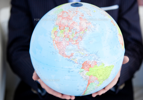Close up of a business person holding a terrestrial globeの素材 [FYI00482152]