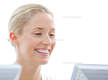 Portrait of a smiling businesswoman working at a computerの写真素材 [FYI00482154]