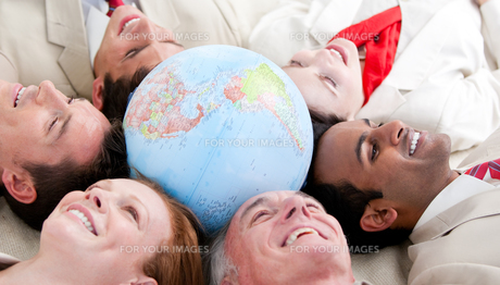Business people lying around a globeの写真素材 [FYI00482157]