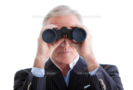 Serious businessman looking through binoculars standingの写真素材 [FYI00482158]