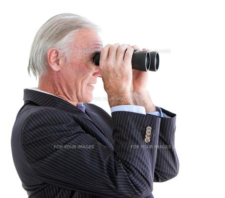 Confident businessman looking through binocularsの写真素材 [FYI00482160]