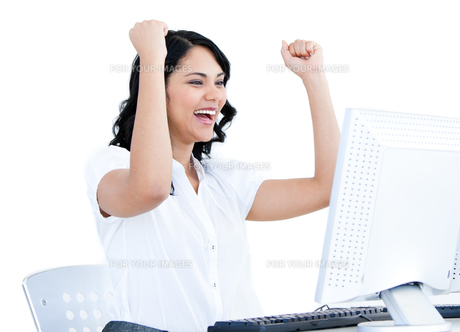 Happy businesswoman punching the air in front of her computerの写真素材 [FYI00482171]