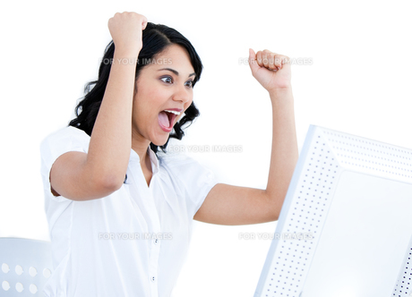 Positive businesswoman punching the air in front of her computerの写真素材 [FYI00482176]