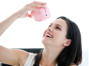 Cute businesswoman looking at a piggybankの写真素材 [FYI00482179]