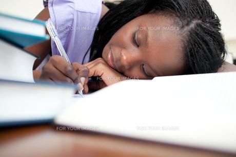 Tired teen girl doing her homeworkの写真素材 [FYI00482186]
