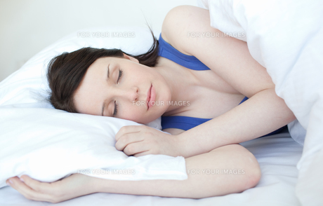 Beautiful young woman sleeping on a bedの素材 [FYI00482188]