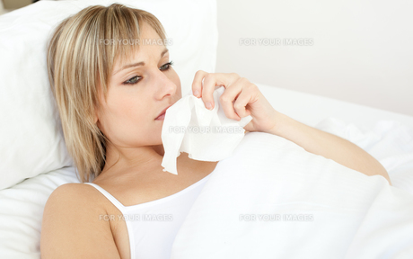 Upset sick woman blowing lying on her bedの写真素材 [FYI00482189]