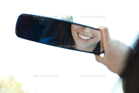 Smiling woman  looking in the rearview mirrorの素材 [FYI00482199]