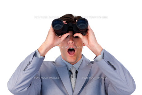 Suprised businessman looking through binocularsの写真素材 [FYI00482201]