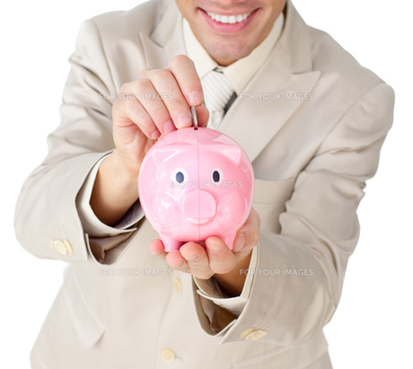 Close up of a businessman saving money in a piggybankの写真素材 [FYI00482221]