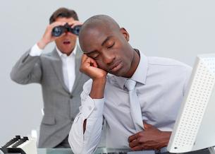 Businessman annoyed by a man looking through binocularsの写真素材 [FYI00482232]