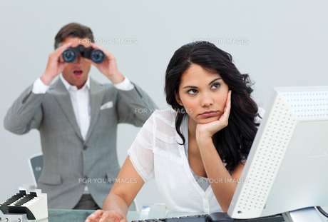 Brunette businesswoman getting bored and her manager looking through binocularsの写真素材 [FYI00482234]