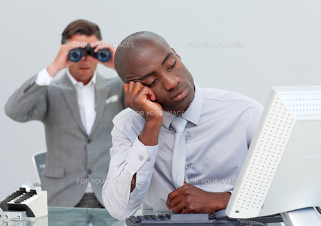 Unhappy businessman getting bored and his manager looking through binocularsの写真素材 [FYI00482235]