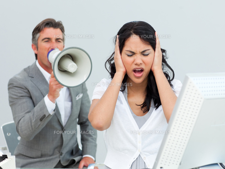 Furious manager shouting through a megaphone in a colleagues earsの素材 [FYI00482236]