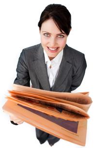 Assertive businesswoman reading a newspaperの写真素材 [FYI00482249]