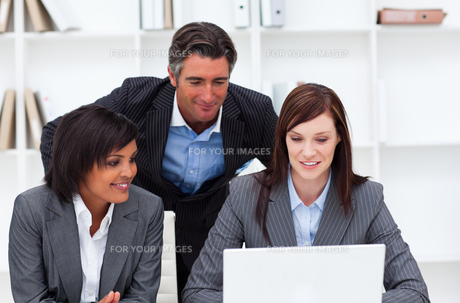 Charming businesswomen and their colleague working at a laptopの写真素材 [FYI00482263]