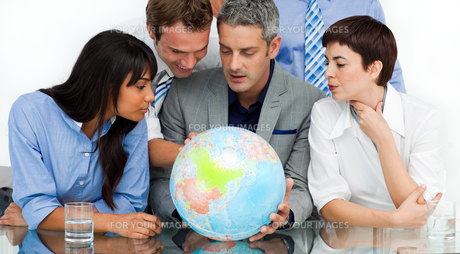 International business people looking at a terrestrial globeの写真素材 [FYI00482273]