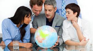 International business people looking at a terrestrial globeの写真素材 [FYI00482273]