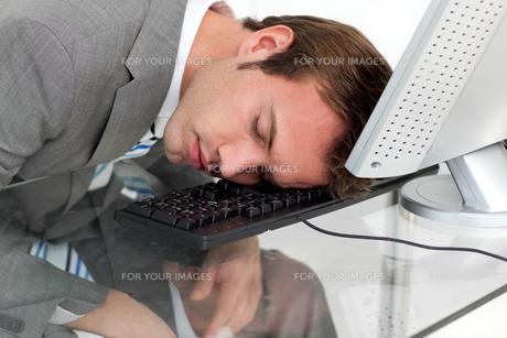 Closeep of a tired businessman sleeping on his deskの素材 [FYI00482279]