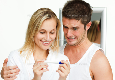 Happy woman and frightened man examining a pregnancy testの素材 [FYI00482282]