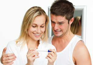 Happy woman and frightened man examining a pregnancy testの写真素材 [FYI00482282]