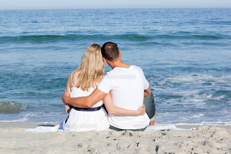 Affectionate couple sitting on the sand at the beachの素材 [FYI00482288]