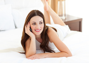 Brunette woman on phone lying on bedの写真素材 [FYI00482291]