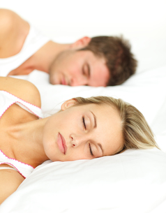 Portrait of a relaxed couple sleeping on their bedの写真素材 [FYI00482294]
