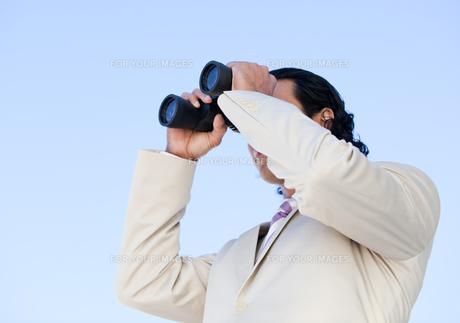Portrait of an handsome business man looking through binocularsの素材 [FYI00482306]